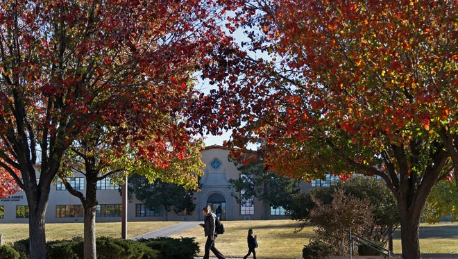 NMSU students walk to class under late fall foliage on campus.