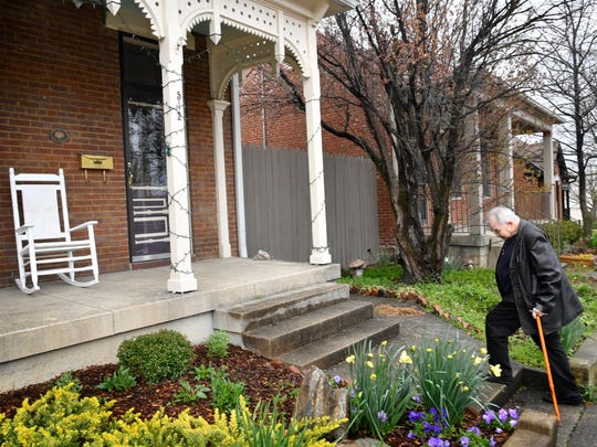 John Prine, still recovering from a knee replacement, uses a cane to climb the steps to his office on March 20, 2018, in Nashville.