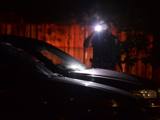 An officer checks cars at the scene of a shooting near Laurel Street and College Avenue on July 21, 2015 in Fort Collins