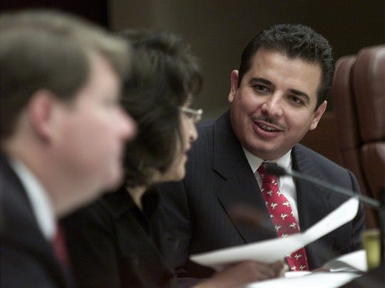 In this 2002 photo, former County Commissioner Carlos Aguilar, right, speaks with County Judge Dolores Briones.