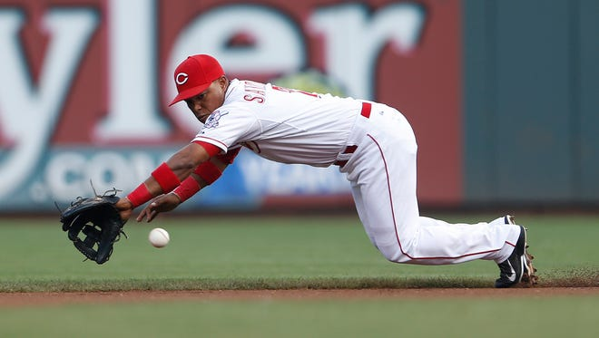 Reds shortstop Ramon Santiago dives for a line drive off the bat of Pirates right fielder Travis Snider during the first inning Saturday.