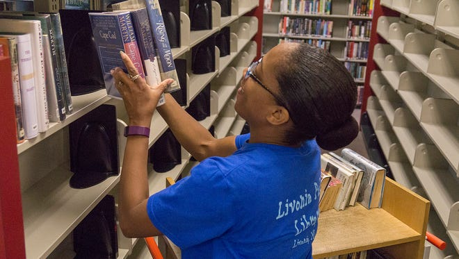 Eurecha Andrews reshelves books during the reorganization.