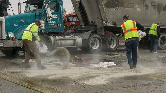 Livonia DPW crew cleans up fluids that leaked from the truck.