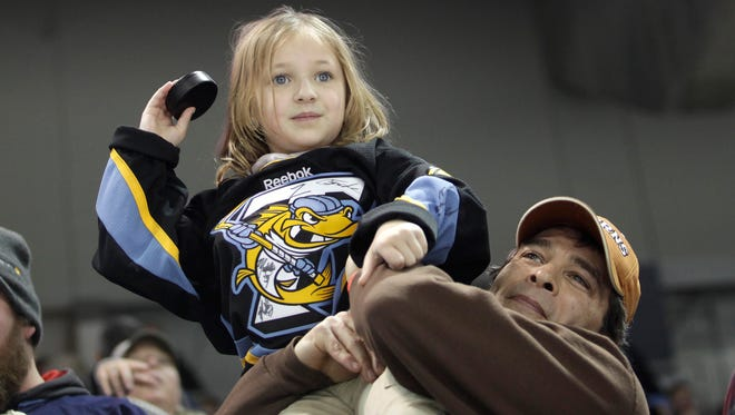 Ray Dile holds his daughter, Sydney, 7, while she throws a hockey puck on the ice between periods during a promotional event for fans.
