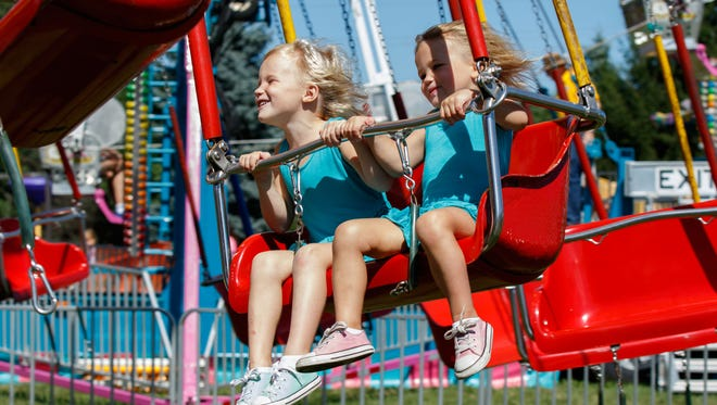Ella Torgersen (left) and her sister Aimee, both of Hartland, enjoy a carnival ride during the annual Fall Festival at St. Charles Parish and School in 2015. This year's event will run from Friday through Sunday, Sept. 8-10.