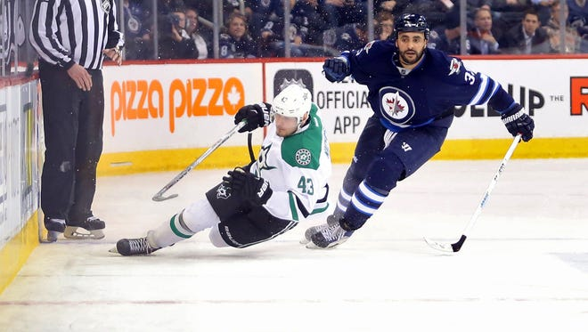 Winnipeg Jets defenseman Dustin Byfuglien (33) chases a loose puck with Dallas Stars right wing Valeri Nichushkin (43) during the third period at MTS Centre.
