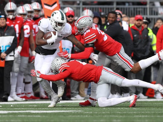 Michigan State's LJ Scott is tackled by Ohio State