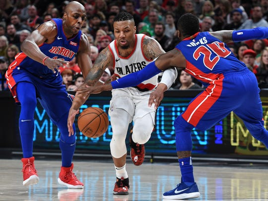 Portland Trail Blazers guard Damian Lillard drives between Detroit Pistons forward Anthony Tolliver, left, and guard Dwight Buycks during the second half of an NBA basketball game in Portland, Ore., Saturday, March 17, 2018. The Blazers won 100-87.