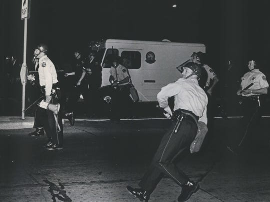 A police officer rears back to hurl a smoke canister to disperse demonstrators near N. Lake Drive and E. North Ave. on July 15, 1970. About 500 rock-throwing youths were driven from Water Tower Park that night. This photo was published in the July 16, 1970, Milwaukee Sentinel.