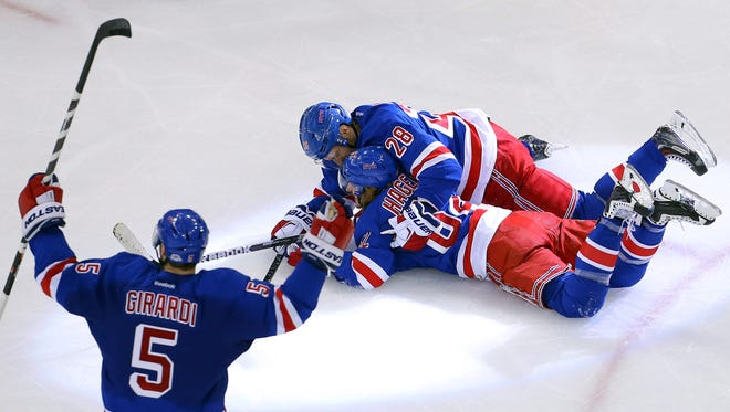 New York Rangers left wing Carl Hagelin (62) is congratulated by teammates center Dominic Moore (28) and defenseman Dan Girardi (5) after scoring the game winning goal against the Pittsburgh Penguins during overtime in Game 5.