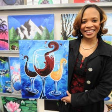 Painting with a Twist owner Michelle Lewis holds up her third-anniversary painting Tuesday night, March 26, 2014. Lewis sketched out this design her self to commemorate their third year in business. Painting with a Twist, located at 200 W. Nine Mile in Ferndale, combines wine and painting with help from artist instructors. Tanya Moutzalias/Special to the Free Press