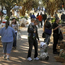 People shop at the Palafox Market at the Dr. Martin Luther King Jr. Plaza on Palafox Street from Chase to Wright streets in downtown Pensacola. The Wednesday market is no longer operating because of the heat, but the Saturday market will continue.