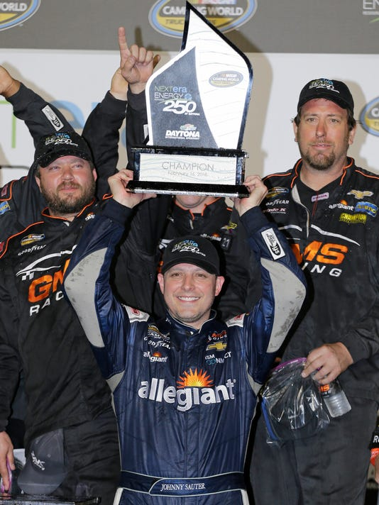Johnny Sauter raises the trophy in Victory Lane after winning the NASCAR Truck Series auto race at Daytona International Speedway in Daytona Beach, Fla., Friday, Feb. 16, 2018. (AP Photo/Terry Renna)