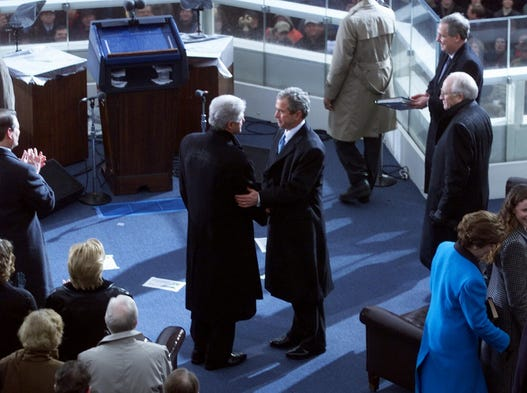 Former President Bill Clinton shakes hands with newly sworn in President George W. Bush on Jan. 21, 2001.