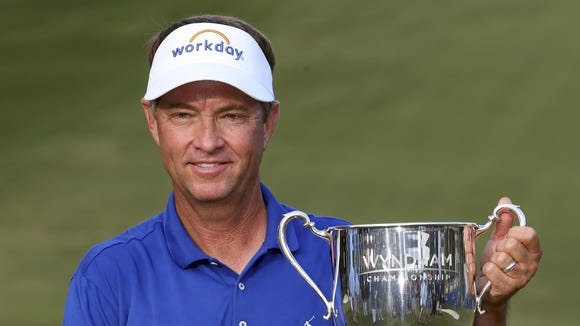 Davis Love III poses with the trophy after winning