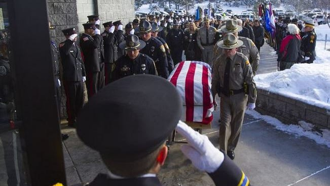 Police officers salute as the coffin of Flagstaff Officer Tyler Stewart enters Christ's Church of Flagstaff in Flagstaff, Ariz., on Friday, January 2, 2015. Stewart was shot and killed responding to a domestic violence investigation on Saturday.
