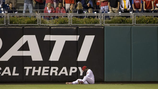 Phillies left fielder Domonic Brown sits on the ground in pain after diving for a ball in the top of the fifth inning Wednesday against the Pittsburgh Pirates in Philadelphia.