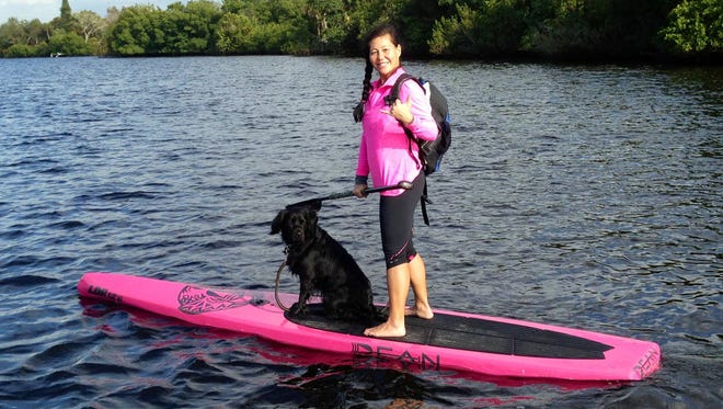 Kat Lucchesi and her dog Charlie go paddleboarding.