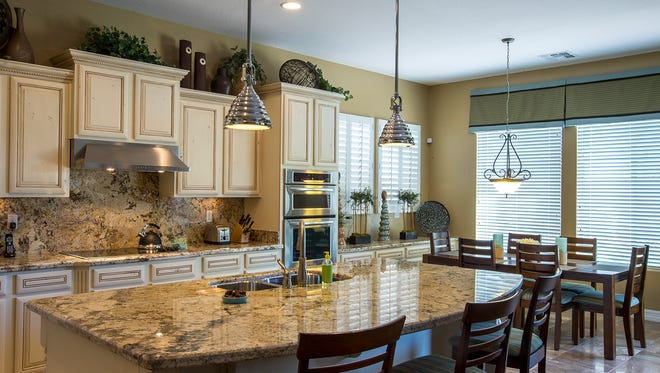The kitchen area features granite countertops and back splashes in the Litchfield Park home of Celeste and Graham Thatcher. The Thatchers recently purchased a 3,077 square foot, 3 bedroom 3.5 bath with guest suite, fully furnished model home in a closed-out West Valley Shea Homes subdivision.
