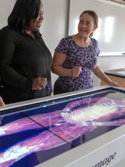 Instructor Penny Schwanz demonstrates the Anatomage machine to anatomy student Taneika Kennedy (left). MATC's new Anatomage table which renders the human body in 3D helps students visualize anatomy.  There are the actual bodies of 3 individuals encoded into the machine.  This image is of the caucasion male named Carl.  The image on screen can be dissected with a stylus, layer by layer and replaces dissecting a human cadaver.