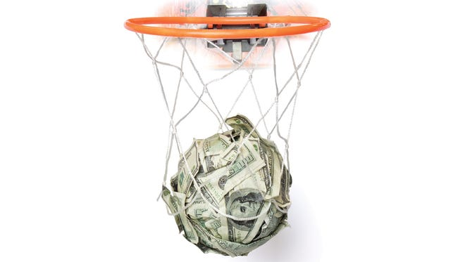 A photo illustration of a moneyball through a basketball net.
