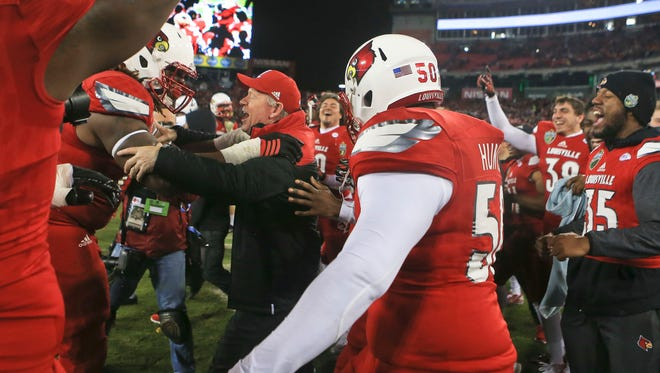 Louisville Bobby Petrino celebrates with his players after their 2015 Music City Bowl win over Texas A&M 27-21 in Nashville.