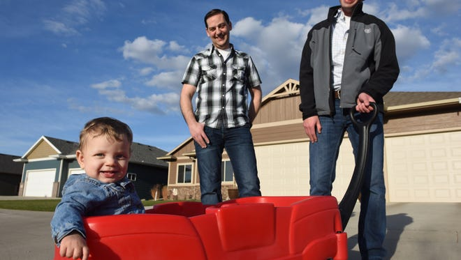 Greg Roling (center) and Larry Sandal take a stroll with their 9-month-old adopted daughter, Emmersyn, in southwest Sioux Falls.