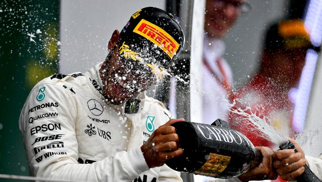 Lewis Hamilton celebrates on the podium during the Formula One Grand Prix of Great Britain at Silverstone.