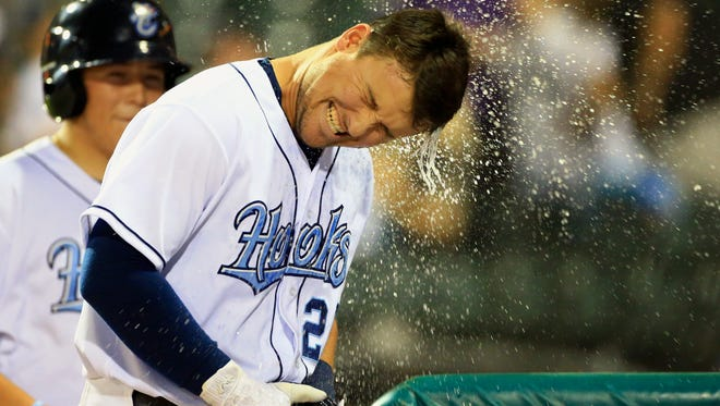 Hooks' JD Davis gets splashed with water after hitting a home run against Arkansas on Saturday, April 15, 2017, at Whataburger Field in Corpus Christi.