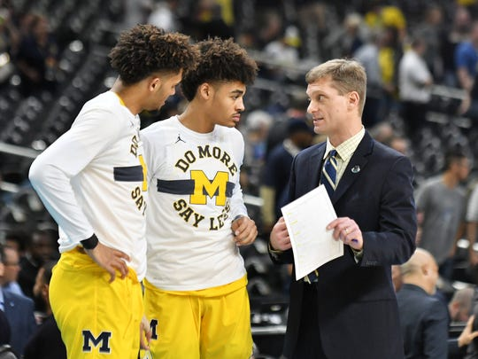 Michigan assistant coach Luke Yaklich, right, talks with Isaiah Livers, left, and Jordan Poole before a game this past season.