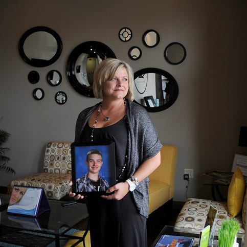 Kristine Brugh poses with a portrait of her late son Taylor Brugh, who took his life in 2013. Kristine opened Spa Nala in Sartell in part because of the memory of her son.
