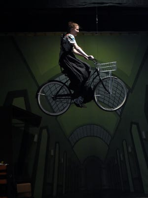 """Emily Hartman soars through the air while playing """"Miss Gulch"""" as Reitz High School students rehearse the """"The Wizard of Oz"""" at the school in Evansville recently."""