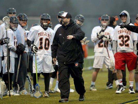 York Suburban head coach Luke Beam, center, reacts after a Trojans' goal in the first half of a boys lacrosse game on Thursday. York Suburban defeated York Catholic 12-7. This is Beam's first season with the Trojans.