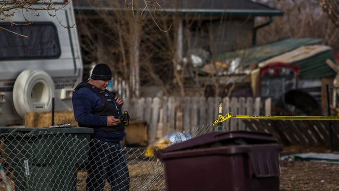 An officer waits outside an Enoch home in the aftermath of an armed standoff Tuesday morning, Jan. 19, 2016.