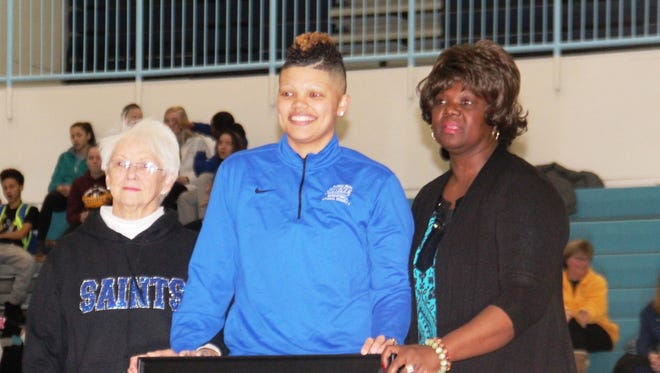 Sydney Moss with her framed jersey and grandmothers Margaret Offutt, left, and Maxine Moss.