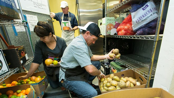 El Caldito Soup Kitchen volunteers Norma Rodriguez, left, Richard Hiss, center, and Damien Jones organize produce and other food items on Wednesday, January 27, 2016, in the back pantry of the soup kitchen. Food donations are constantly sorted and rotated as they are delivered to the location.