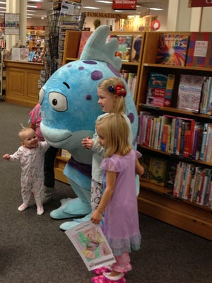 "Lydia Wittmann (left), 16 months, of Delta Township, is delighted to meet the Mr. Fish character from one of her favorite picture books, ""The Pout-Pout Fish,"" at Schuler Books and Music in the Meridian Mall."