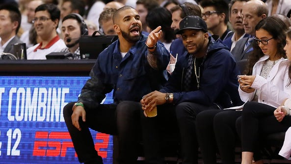 Recording artist Drake (left) reacts during game three