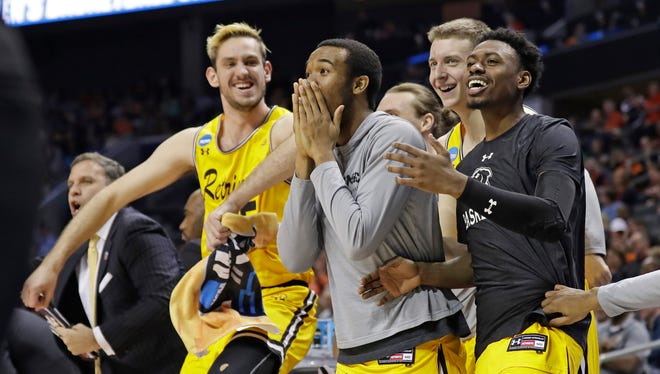 UMBC players celebrate a teammate's basket against Virginia.
