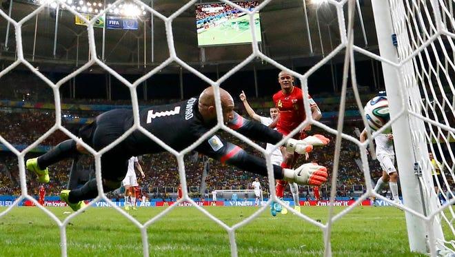 U.S. goalkeeper Tim Howard blocks a shot from Belgium's Vincent Kompany. Howard had 16 saves in the Americans' 2-1 defeat.