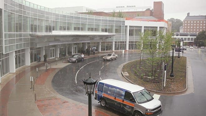 Vehicles pass in front of the University of Virginia Medical Center in Charlottesville.