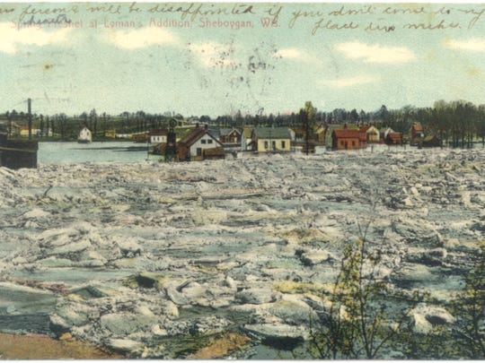 Postcard showing the Sheboygan River backed up with ice jams near the flats.