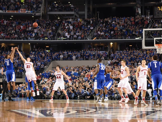 Kentucky Wildcats guard Aaron Harrison (2) hits a three-point shot over Wisconsin Badgers guard Josh Gasser (21) in the second half during the semifinals of the Final Four in the 2014 NCAA Mens Division I Championship tournament at AT&T Stadium.