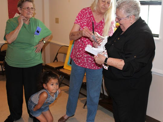 Moni Zills, center, tells retiring Metropolitan Exodus Community Church pastor Margaret Warn-Walker, right, about the knife given to her as a farewell gift. It was made by the father of Madelyn Lance. Sissy Heathcott, left, was another of the guests at the June 9 reception for Warn-Walker.