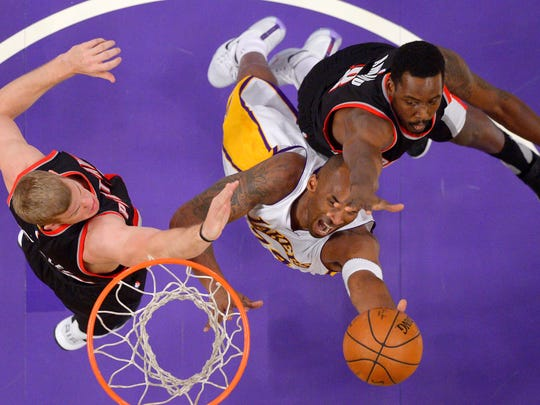Los Angeles Lakers forward Kobe Bryant, center, shoots as Portland Trail Blazers center Mason Plumlee, left, and forward Al-Farouq Aminu defend during the first half of an NBA basketball game, Sunday, Nov. 22, 2015, in Los Angeles.