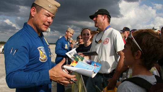 A 2010 photo provided by the U.S. Navy shows Capt. Greg McWherter signing autographs after an air show.
