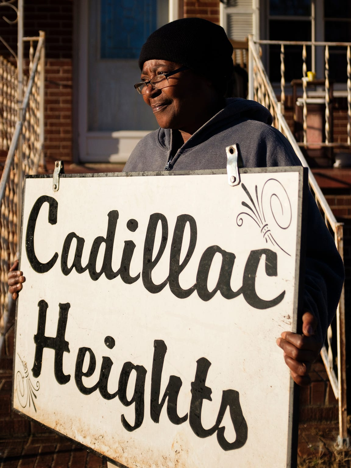 Sandra Williams holds a Cadillac Heights sign in front