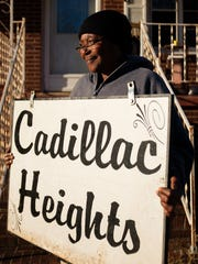 Sandra Williams holds a Cadillac Heights sign in front of her home. Williams keeps two of the neighborhood signs out of sight on her property. She says residents have had issues with their neighborhood signs being stolen.