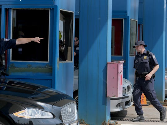 """A U.S. Customs and Border Protection officer at the Lewiston-Queenston Bridge directs a driver. Mark MacVittie, acting director at the Port of Buffalo, said officers are """"welcoming, whether or not they say the words or there's a smile."""""""