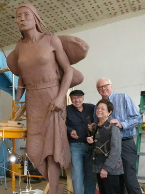 Left to right, artist R.T. 'Skip' Wallen, Kate Miller and John Miller are shown with one of three figures of Wallen's Spirit of the Rivers sculpture.